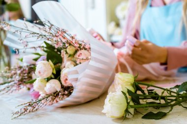 partial view of female florist wrapping flower bouquet with roses in paper