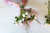 Fotografie top view of female florist arranging bouquet with white tulips and roses on table