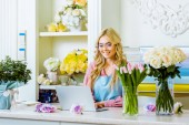 beautiful smiling female flower shop owner in glasses sitting at desk and using laptop