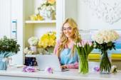 krásný usměvavý samičí květ majitel obchodu v brýlích sedí u stolu a pomocí přenosného počítače