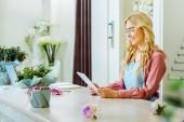 krásný usměvavý samičí květ prodavačů v brýlích pomocí digitálních tabletu na přepážce
