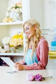 selective focus of beautiful female flower shop owner in glasses using digital tablet at counter