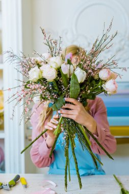 female florist holding bouquet with white roses in front of face in flower shop