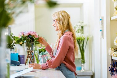 beautiful female florist adjusting bouquet of pink roses in flower shop