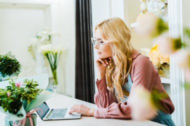 beautiful pensive female florist in glasses using laptop in flower shop