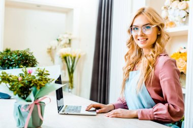 beautiful female florist in glasses using laptop in flower shop and looking at camera