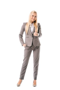 Smiling businesswoman in grey suit showing thumb up isolated on white stock vector