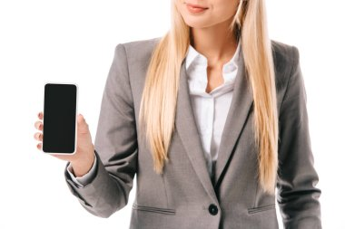 Cropped view of businesswoman showing smartphone with blank screen, isolated on white stock vector