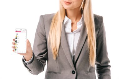 cropped view of businesswoman showing smartphone with apple music app, isolated on white