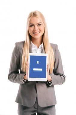 beautiful blonde businesswoman showing digital tablet with facebook app on screen, isolated on white
