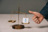 partial view of businessman showing thumbs up near scales of justice and male signs, gender stereotypes concept