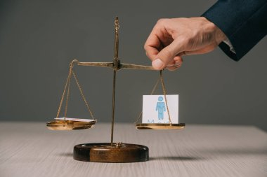 cropped view of businessman with scales of justice and male signs, gender stereotypes concept
