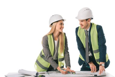 Architects in safety vests and hardhats working with blueprints, isolated on white stock vector