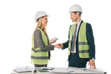 architects in safety vests and hardhats making deal and shaking hands, isolated on white