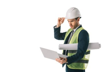 Male engineer in hardhat and safety vest holding blueprint and using laptop, isolated on white stock vector