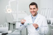 smiling dentist squeezing toothpaste on toothbrush in dental clinic
