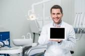 Veselý zubař v bílém plášti drží digitální tablet s prázdnou obrazovkou