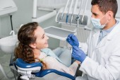 dentist in mask and latex gloves standing near smiling woman in dental clinic