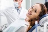 Fotografie Selektiver Fokus der schönen Frau in Zahnspangen während der Untersuchung der Zähne in der Nähe des Zahnarztes
