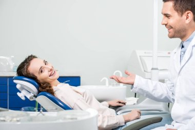 cheerful woman in braces smiling near handsome dentist in clinic