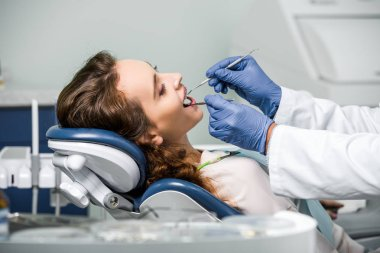 cropped view of dentist in latex gloves examining teeth of woman in dental clinic
