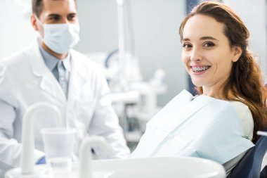 selective focus of woman in braces smiling with dentist standing in mask on background