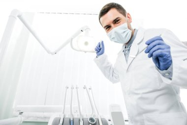 dentist in latex gloves and mask holding dental instrument and dental lamp