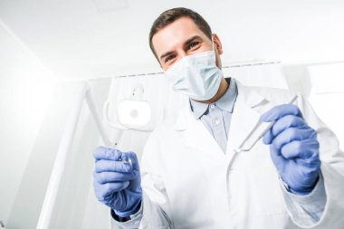dentist in latex gloves and mask holding dental instruments in hands