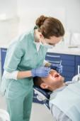 Fotografia Dentista femminile in maschera e lattice guanti esaminando il paziente con la bocca aperta