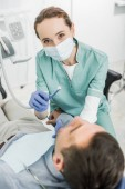 female dentist in mask holding dental drill while working with patient in dental clinic