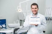 fröhlicher Zahnarzt mit digitalem Tablet und Facebook-App auf dem Bildschirm in Zahnklinik