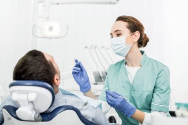 female dentist in mask holding dental instruments near patient in dental clinic
