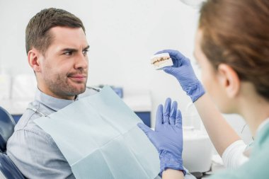 selective focus of confused man looking at teeth model in hand of female dentist