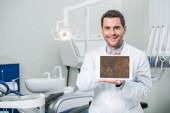 Veselý zubař drží digitální tablet s grafy na obrazovce v zubní klinice