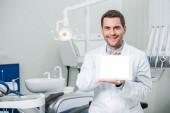 fröhlicher Zahnarzt mit digitalem Tablet mit leerem Bildschirm in Zahnklinik
