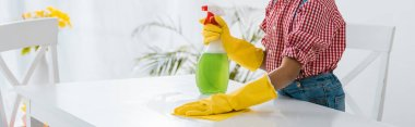african american child with green spray bottle cleaning table in yellow rubber gloves