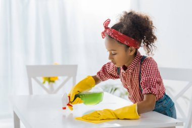 Cute african american child in yellow rubber gloves washing table with cleaning spray and rag stock vector