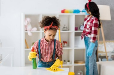 selective focus of cute african american child cleaning table while mother dusting furniture