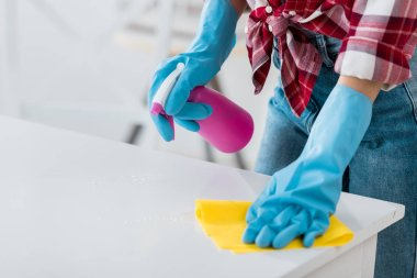cropped view of african american woman cleaning table in blue rubber gloves