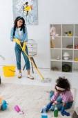 s úsměvem afroamerické ženy, mytí podlahy, když roztomilý dcera čištění koberců