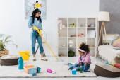 Fotografia bambino afroamericano sveglio pulizia tappeto mentre pavimento di lavaggio della madre con il mop