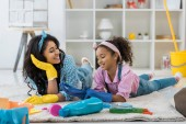 Photo smiling african american mom and cute child in bright rubber gloves lying on carpet