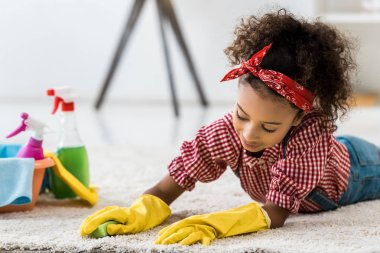 Cute african american child cleaning carpet in yellow rubber gloves stock vector