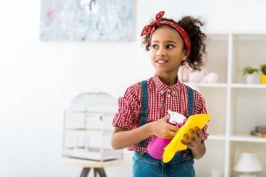 cute african american girl holding yellow rug and pink spray bottle