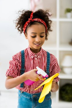 cute african american child spraying cleaning liquid on yellow rag