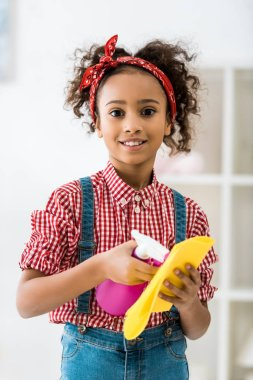 adorable african american child spraying cleaning liquid on yellow rag and looking at camera
