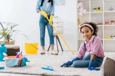adorable african american child cleaning carpet while mother washing floor with map