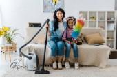 aranyos afro-amerikai gyermeket gazdaság színes duster ülve a kanapé közelében mosolygó anya