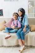 africká americká matka a dítě společně pomocí smartphone, zatímco sedí na gauči doma