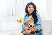 Fotografie beautiful african american woman sitting on sofa and holding teddy bear